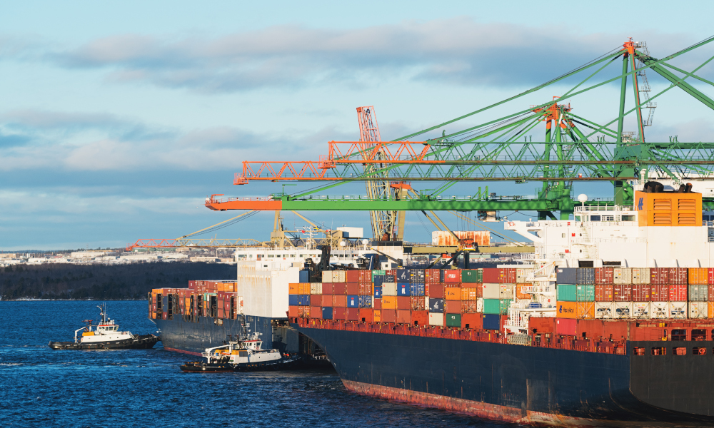 Two tugboats assist a container ship with it's departure from a large container terminal located in Halifax, Nova Scotia.